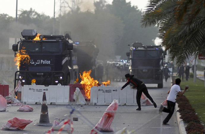 Anti-government protester throws a Molotov cocktail at a riot-police armored personnel carrier during clashes in Diraz