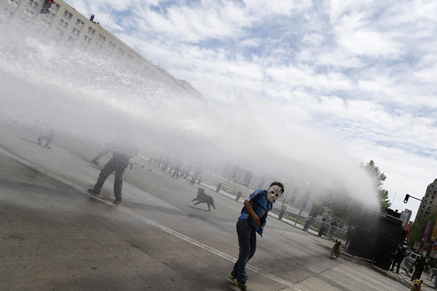 A Mapuche Indian activists dodges a jet of water during a protest against Columbus Day in Santiago