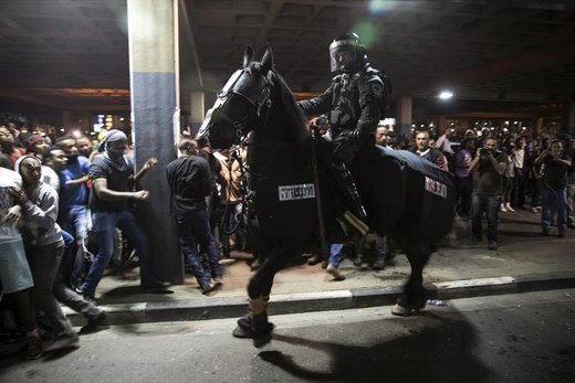 Protesters, whom are mainly Israeli Jews of Ethiopian origin, run away as a policeman on a horse tries to disperse them during a demonstration against what they say is police racism and brutality, after the emergence last week of a video clip that showed policemen shoving and punching a black soldier in a protest at Rabin Square in Tel Aviv May 3, 2015. Israeli mounted police charged hundreds of ethnic Ethiopian citizens and fired stun grenades on Saturday to try to clear one of the most violent protests in memory in the heart of Tel Aviv. REUTERS/Baz Ratner - RTX1BDSA