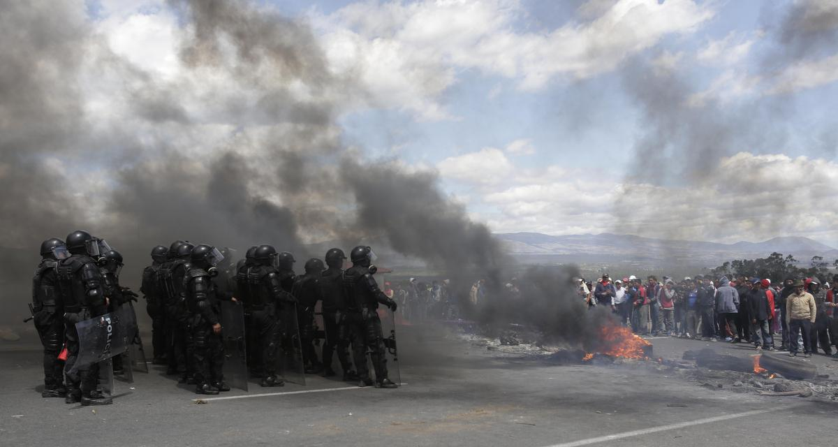 Security forces stand behind a burning road block set up by indigenous protesters from the highlands along the Panamerican Highway during a general strike in the Chasqui area of Ecuador, Thursday, Aug. 13, 2015. A strike by a broad coalition upset with President Rafael Correa virtually paralyzed the capital, provincial cities and stretches of the Panamerican highway. The protesters are indigenous activists, unionists, environmentalists and members of the traditional political opposition. (AP Photo/Dolores Ochoa)
