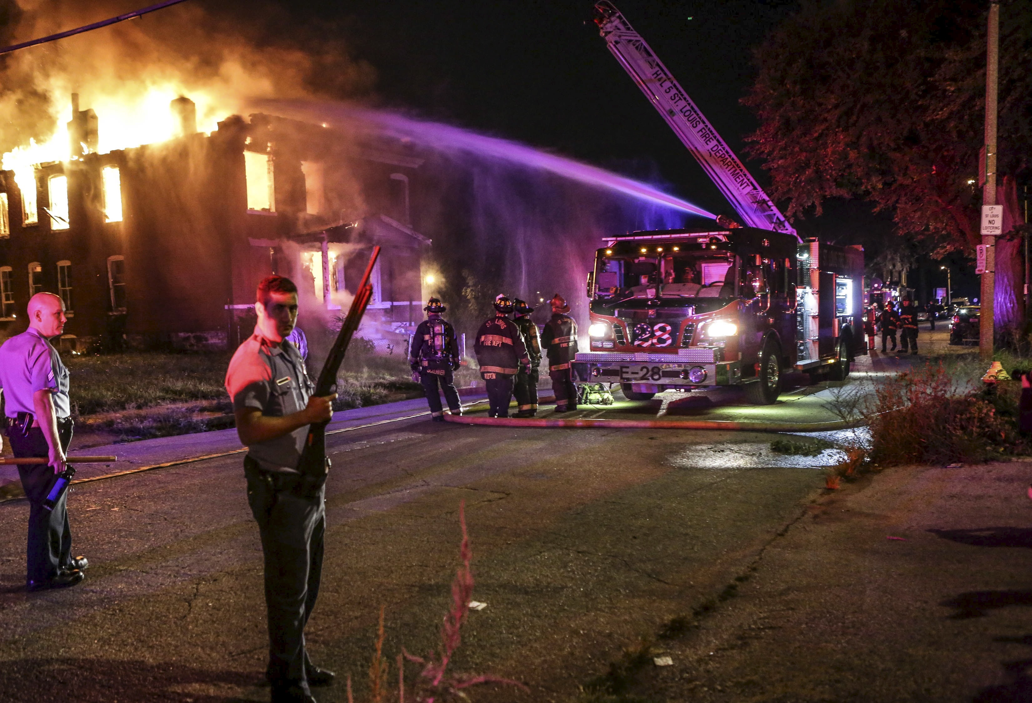 Firefighters attempt to put out a fire at an abandoned building with the protection of St. Louis City Police in St. Louis, Missouri August 19, 2015. According to eyewitness, protesters demonstrating against a police shooting earlier in the day in St. Louis set the building on fire. St. Louis police fatally shot a black teenager on Wednesday who they say pointed a gun at them, and later faced angry crowds, reigniting racial tensions first sparked by the killing of an unarmed black teen in another Missouri town a year ago. REUTERS/Lawrence Bryant TPX IMAGES OF THE DAY - RTX1OVQE