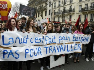 French youths and activists of various youth organisations march with a banner reading 'The night is made for kissing not to work' during a demonstration against proposed changes to labour laws in Paris on March 24, 2016, during a day of action opposing the implementation of new labour legislation. / AFP / DOMINIQUE FAGET