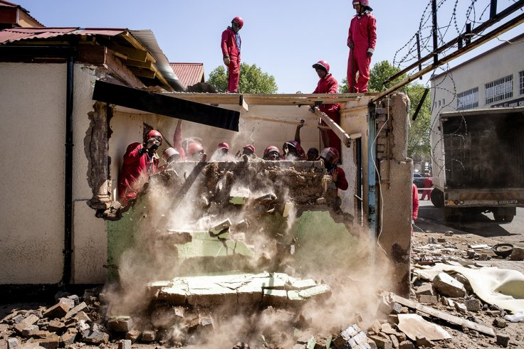 Members of the Red Ants (a local contracted group of workers enforcing municipal orders of demolition or evictions) tear down several structures in central Johannesburg