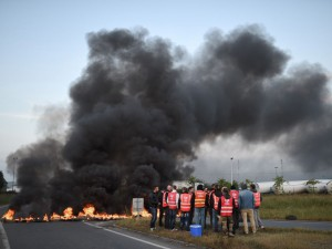 Workers on strike stand next to burning tyres as they block the access to the Total refinery of Donges, western france, on May 17, 2016 to protest against the government's planned labour law reforms. France's Socialist government has bypassed parliament and rammed through a labour reform bill that has sparked two months of massive street protests. / AFP PHOTO / JEAN-SEBASTIEN EVRARD