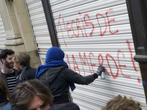 "A demonstrator tags on a Ouest France office "" You write shit"", during a demonstration against the government's planned labour law reforms, in Rennes, on May 17, 2016. The Socialist government last week survived a vote of no-confidence, which was called by the centre-right opposition, after it forced through the labour market reform bill without parliament's approval. / AFP PHOTO / DAMIEN MEYER"