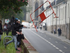 A protestor throws a piece of fence as demonstrators march on May 17, 2016 in Nantes, western France, to protest against the government's planned labour law reforms. Incidents between protestors and police forces escalated around 12h00 in Nantes during a protest against planned employment and labour law reform, during which between 3,500 and 10,000 individuals took part, according to sources. / AFP PHOTO / JEAN-SEBASTIEN EVRARD