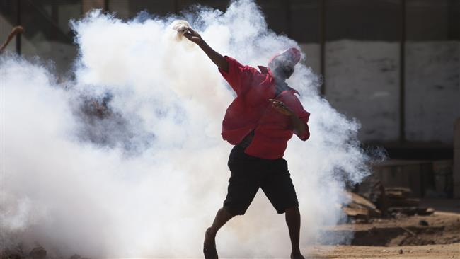 Protester hurls teargas canister back at riot pigs
