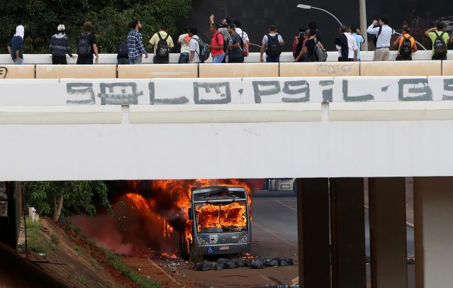 People observe a bus burned by anti-government demonstraters during a protest against the constitutional amendment PEC 55, which limits public spending, in front of Brazil's National Congress in Brasilia, Brazil. REUTERS/Adriano Machado