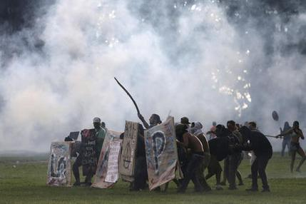 Protesters shield themselves as police fire tear gas at their demonstration outside Congress, where senators planned to vote on a spending cap bill and the lower Chamber of Deputies was considering controversial anti-corruption legislation, in Brasilia, Brazil, Tuesday, Nov. 29, 2016. Brazil, home to Latin America's largest economy, is suffering its worst recession in decades. (AP Photo/Eraldo Peres)